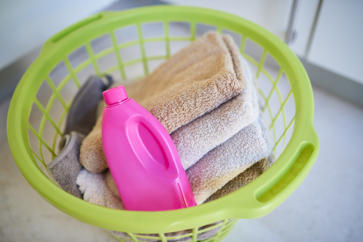 laundry basket filled with towels and detergent