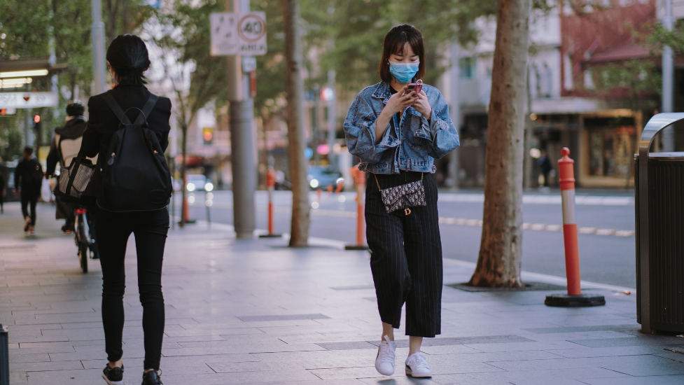 a girl walking down the street wearing a face mask