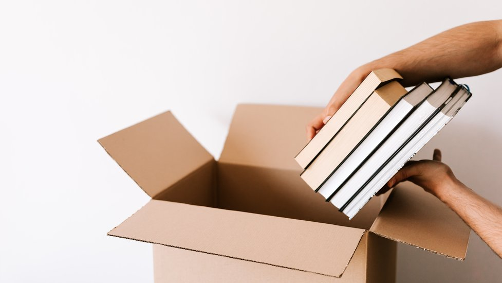 a close up of a person putting books into a box