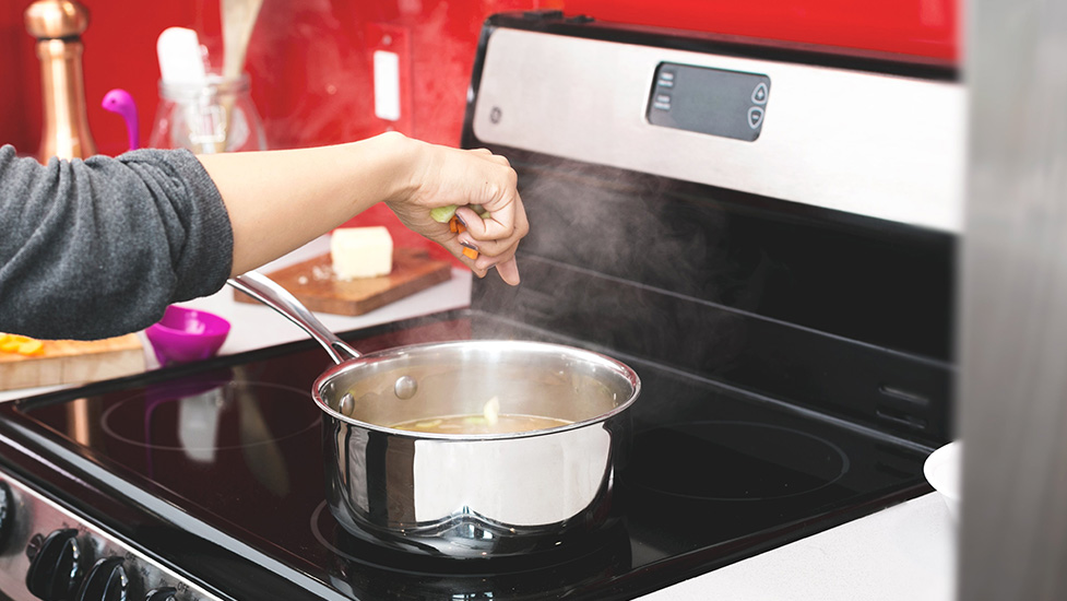 a person cooking on a stove top oven
