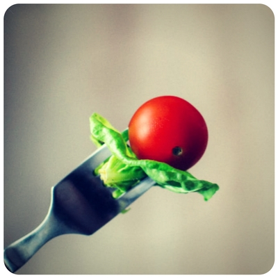 lettuce and a tomato on a fork
