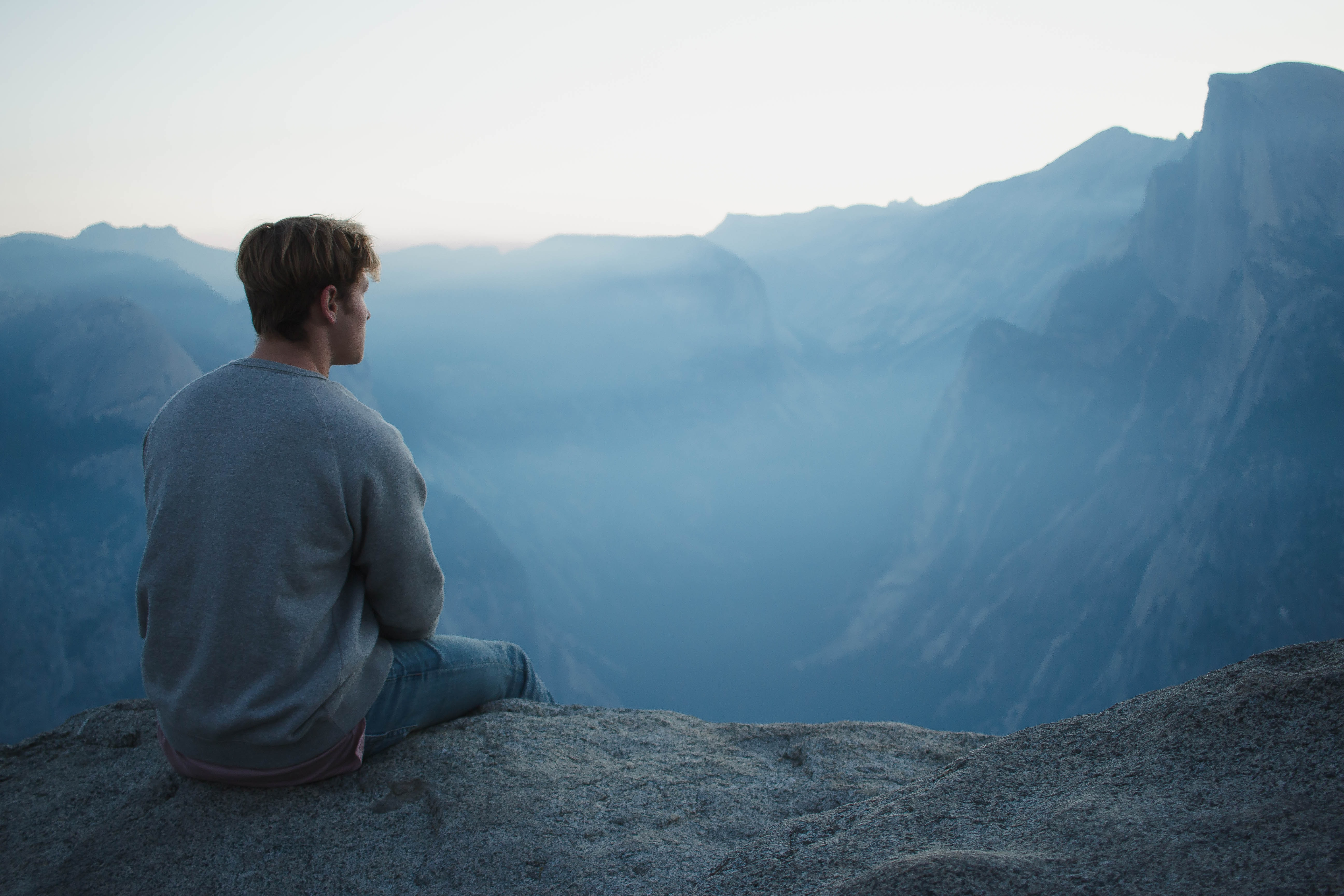 a man sitting in front of a mountain