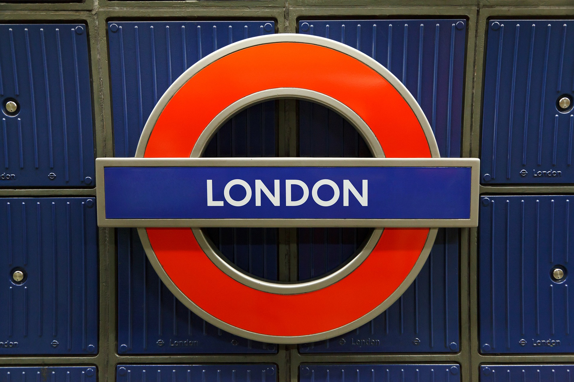 a close up of a metal fence with London Underground in the background