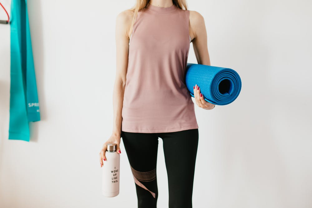 a person standing holding an exercise mat
