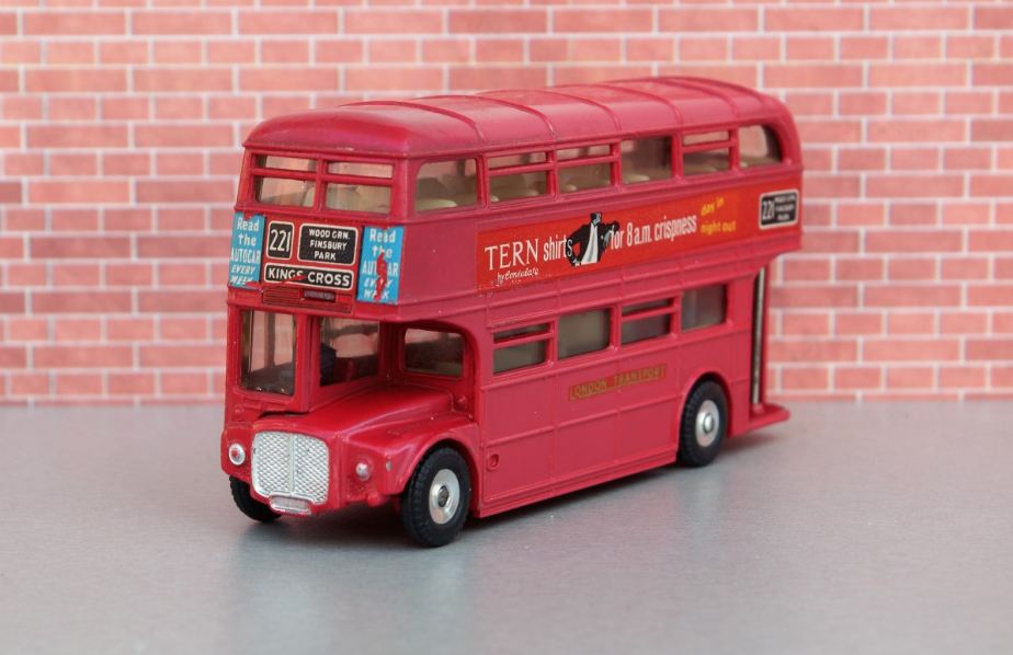 a red double decker bus parked in front of a brick building