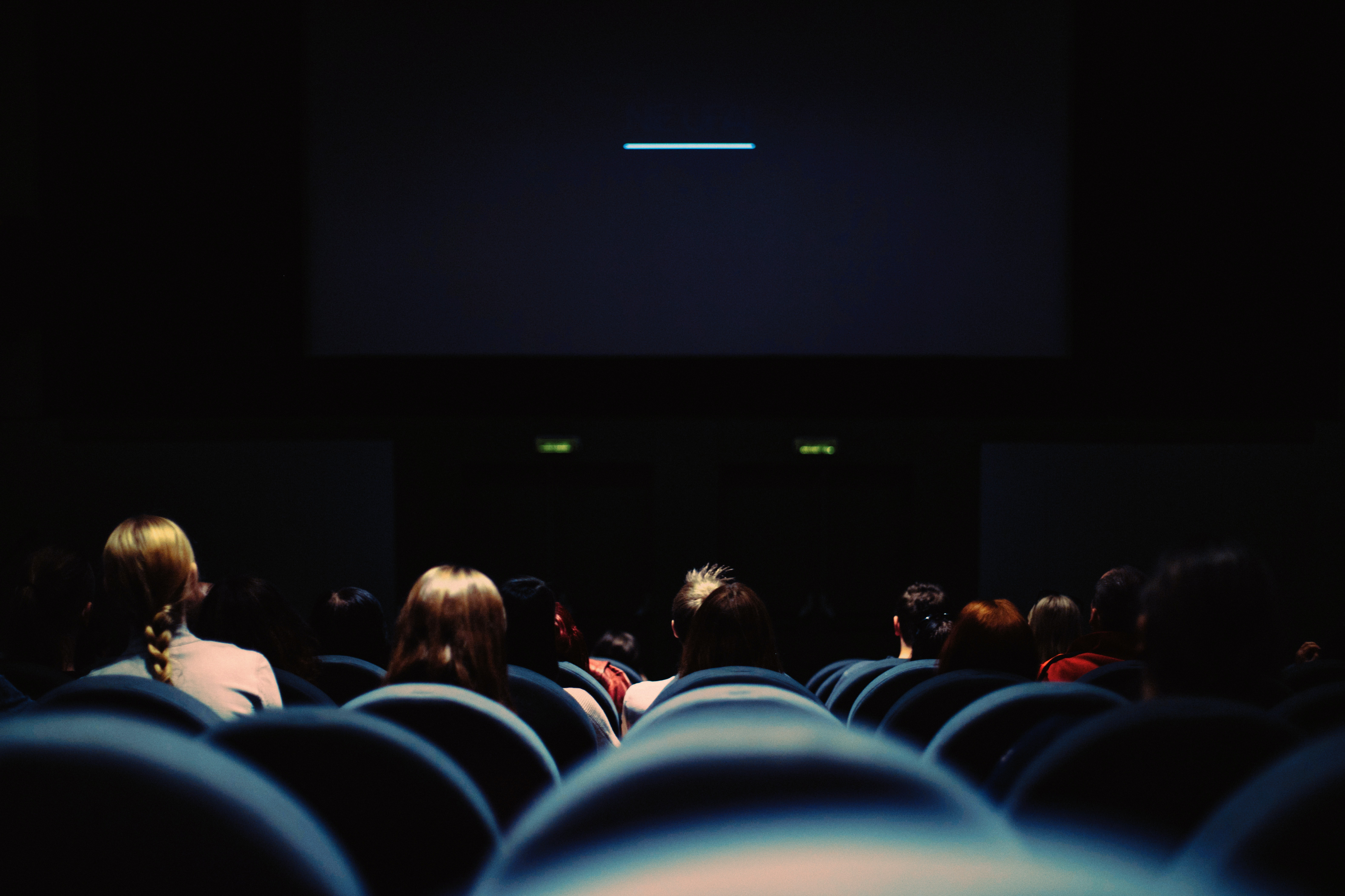 a crowd of people watching television in a dark room