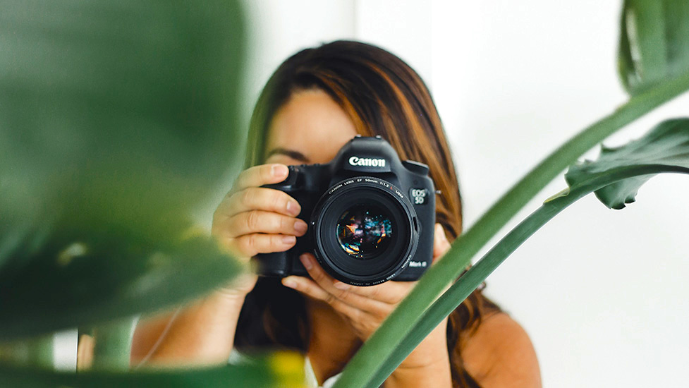 a person holding a camera in front of a mirror posing for the camera