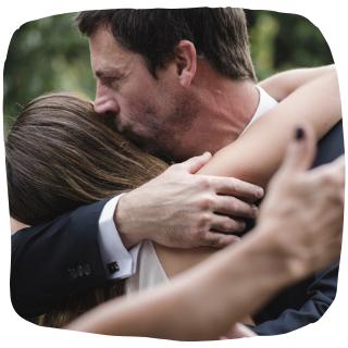 a parent hugging his daughter
