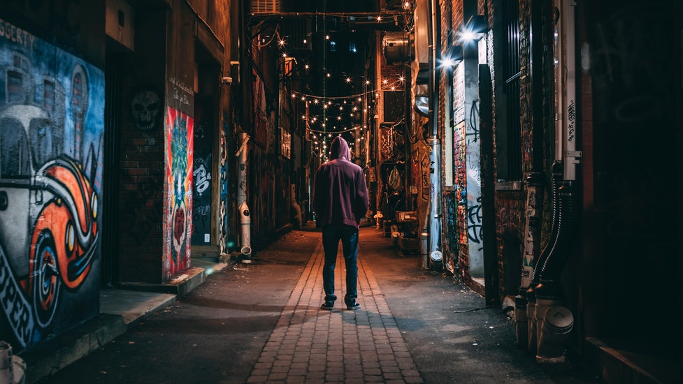a person standing in the middle of an alley