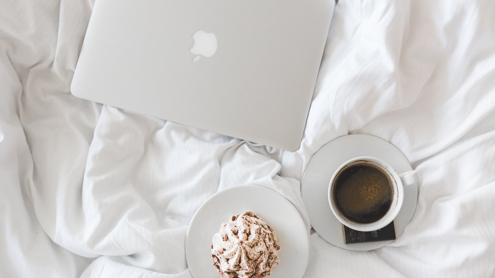 a cup of coffee and a laptop on a bed