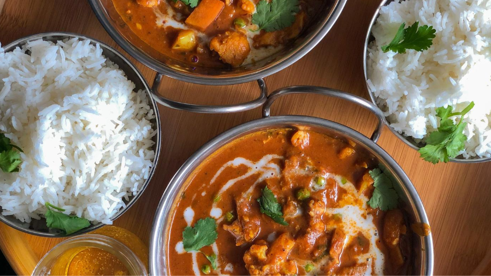 a bowl of curry with two bowls of rice