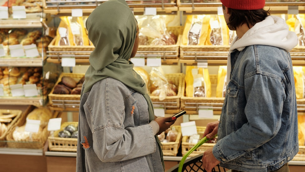 a two people looking at food in a supermarket