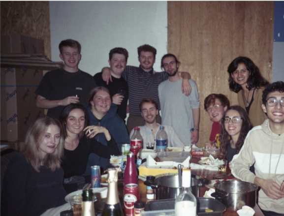 a group of people sitting at a table posing for the camera