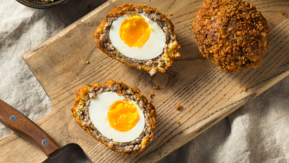 two scotch eggs on a chopping board