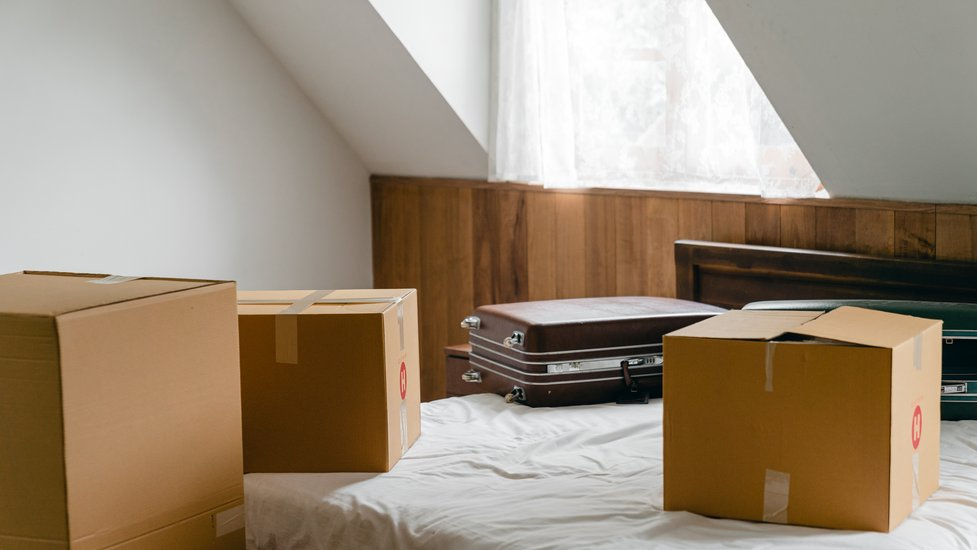 boxes and a suitcase on a bed