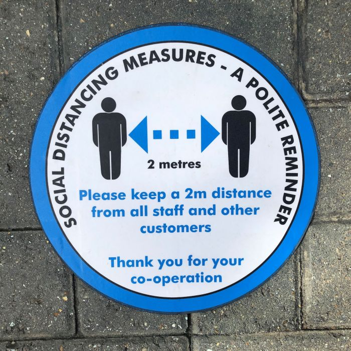 a blue and white sign for social distancing measures