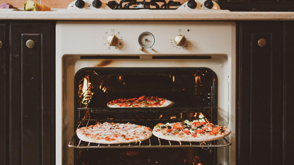 two pizzas going into an open oven