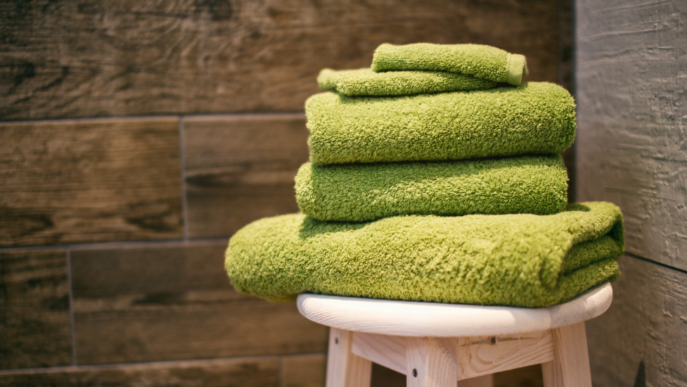 a pile of green towels on a bench