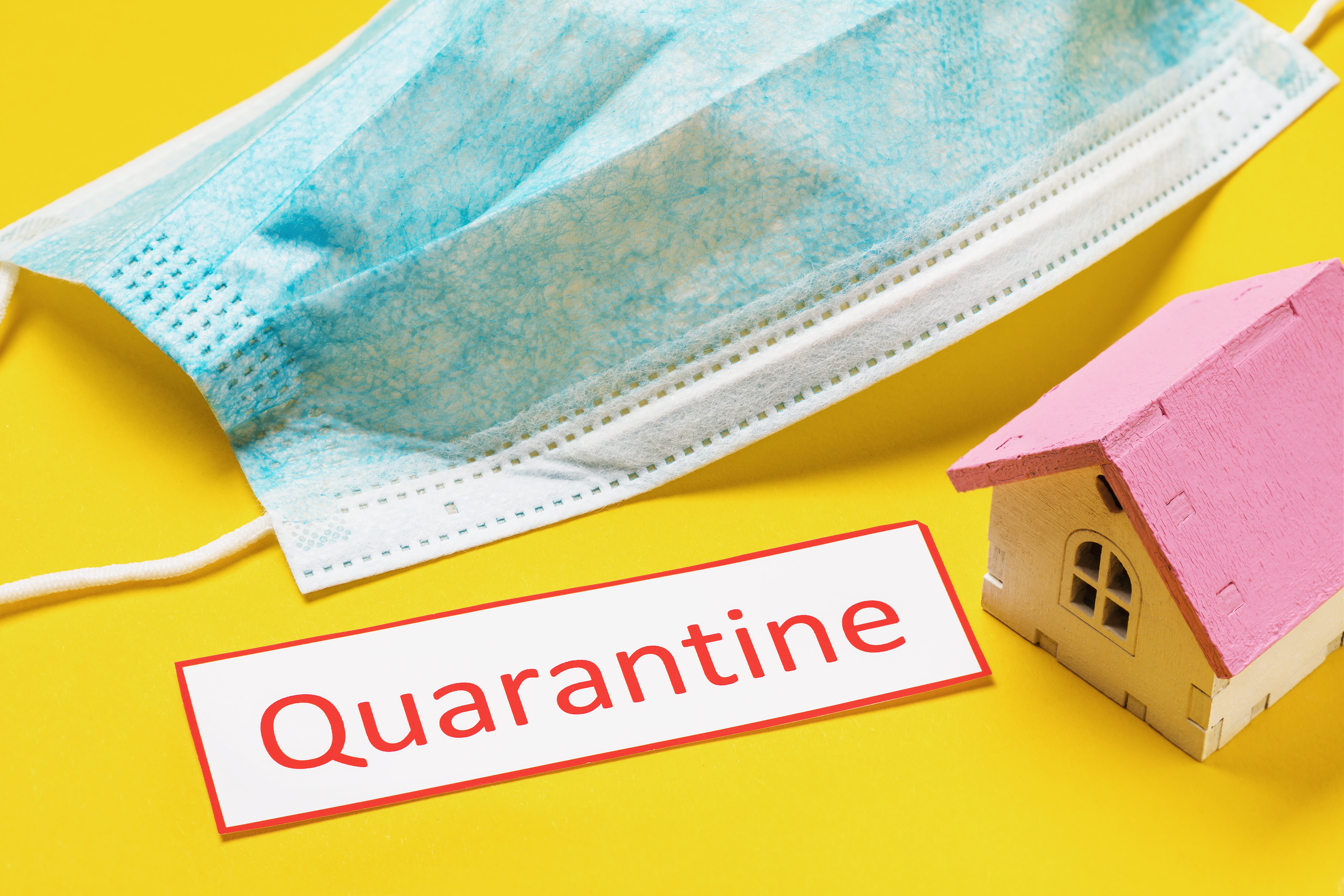 """A medical face mask and the word """"Quarantine"""""""